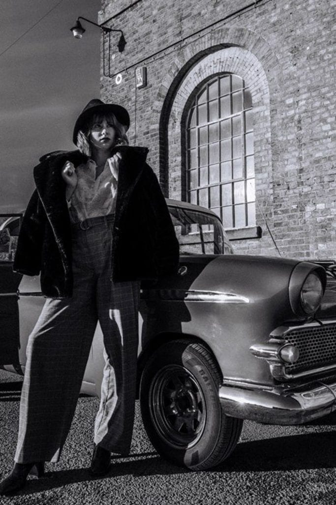 black and white photo of a girl in a fedora hat and black fur coat posing in front of a 1950s car