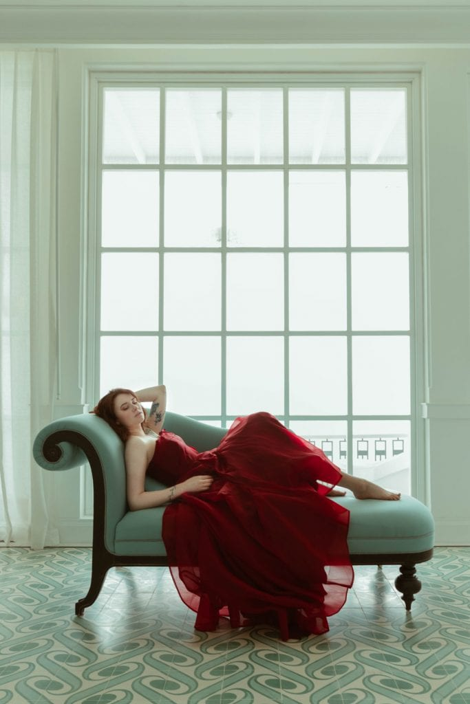 girl lying on chaise lounge in red dress