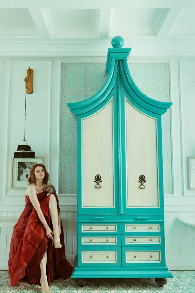 girl in red dress putting shoe on next to blue wardrobe