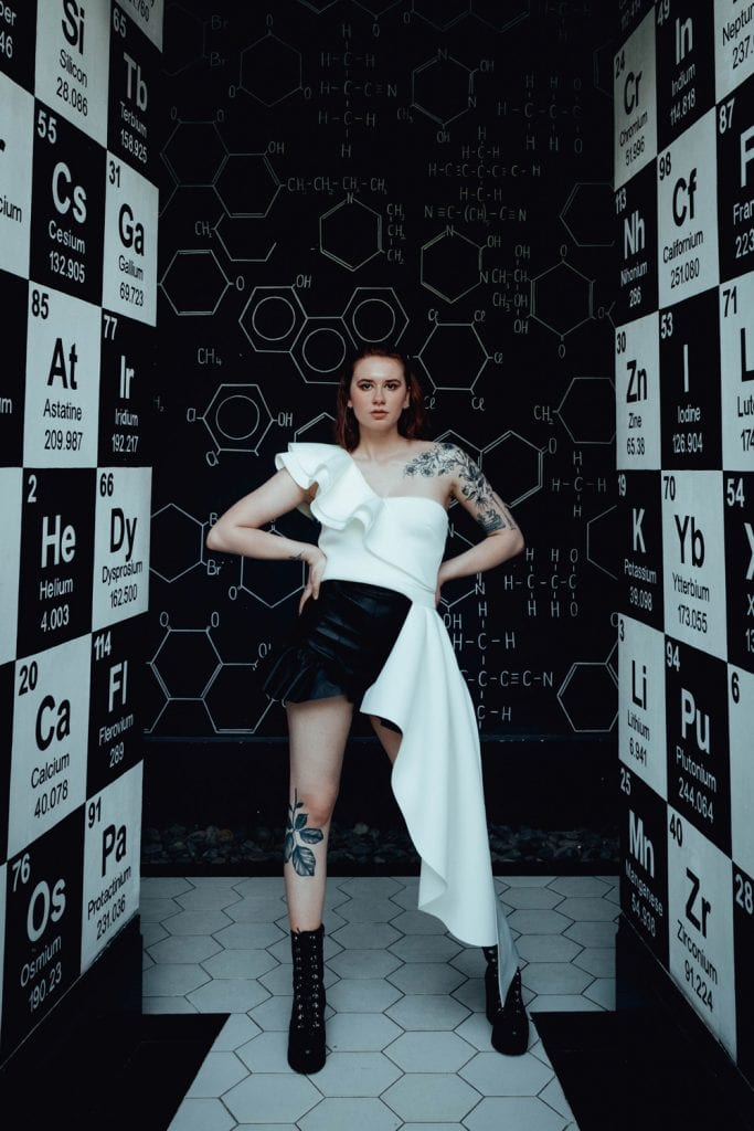 girl standing in hallway, its decorated with chemistry symbols