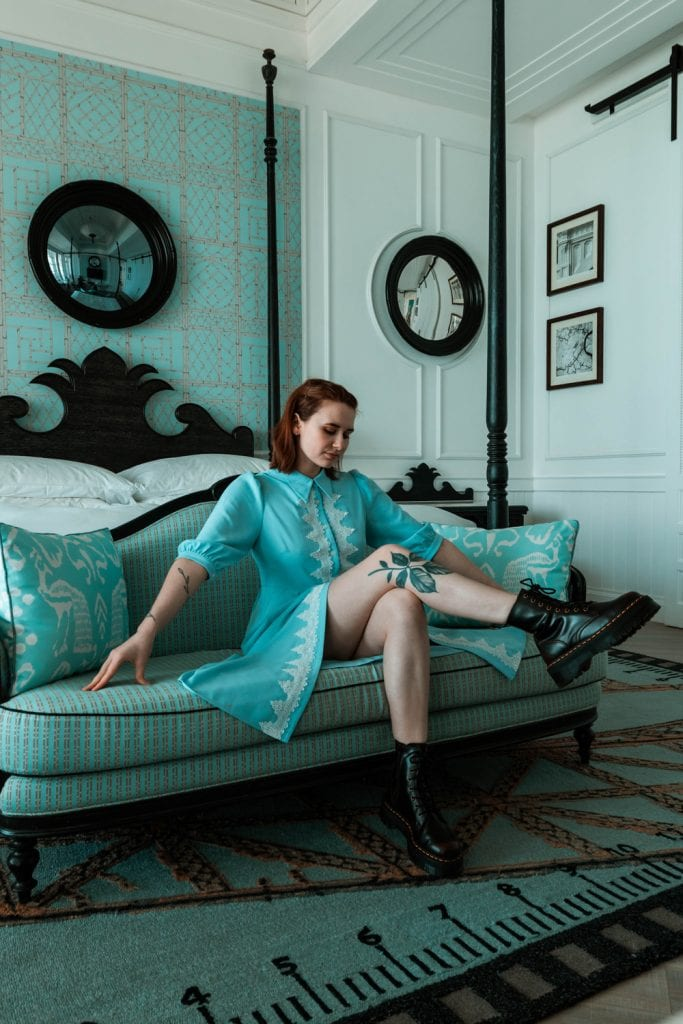 girl in blue dress sitting on sofa in front of bed