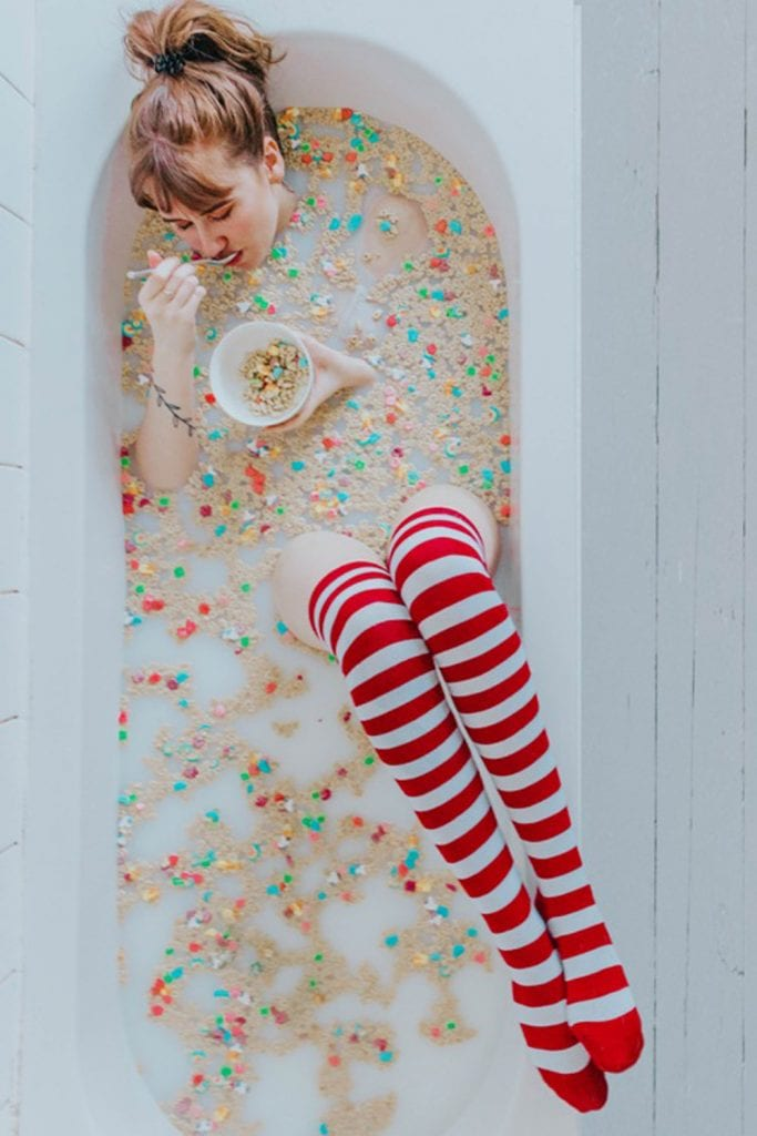 girl sitting in a bath of cereal eating a bowl of cereal wearing red and white stripey socks