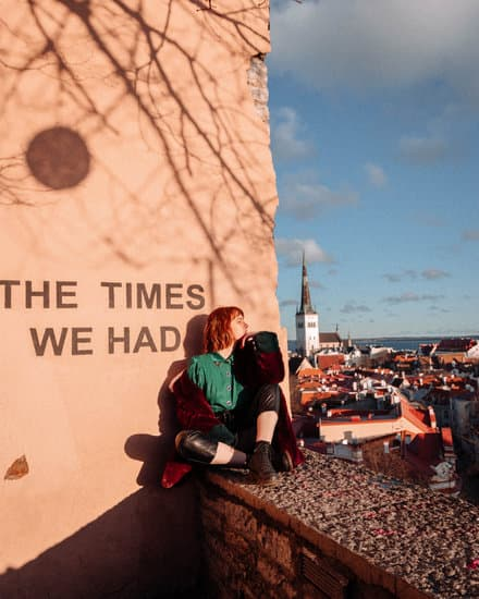 girl sitting on wall in Tallinn looking at the view