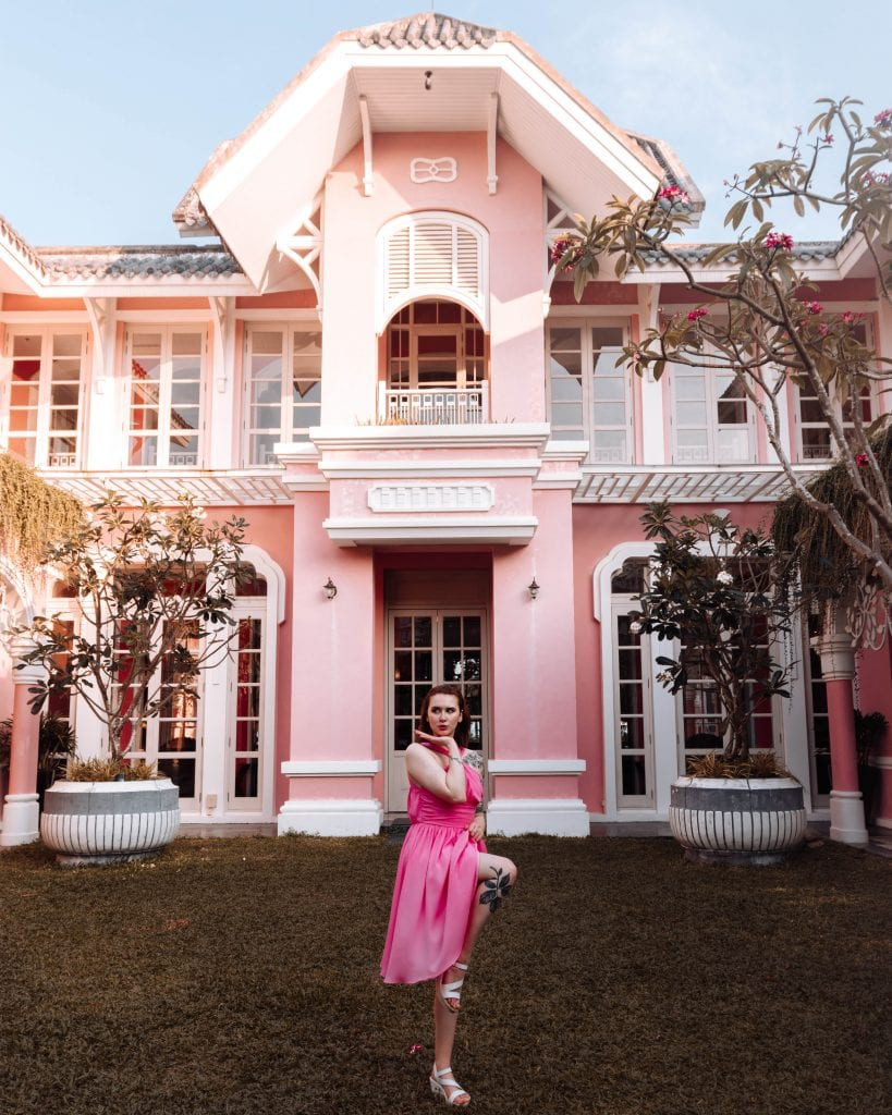 girl stoof in front of a pink building