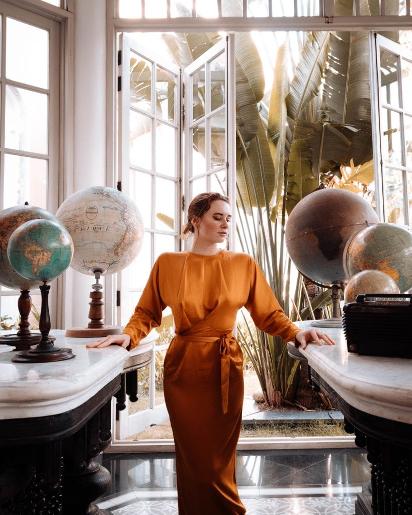 Girl in a yellow dress stood near some globes