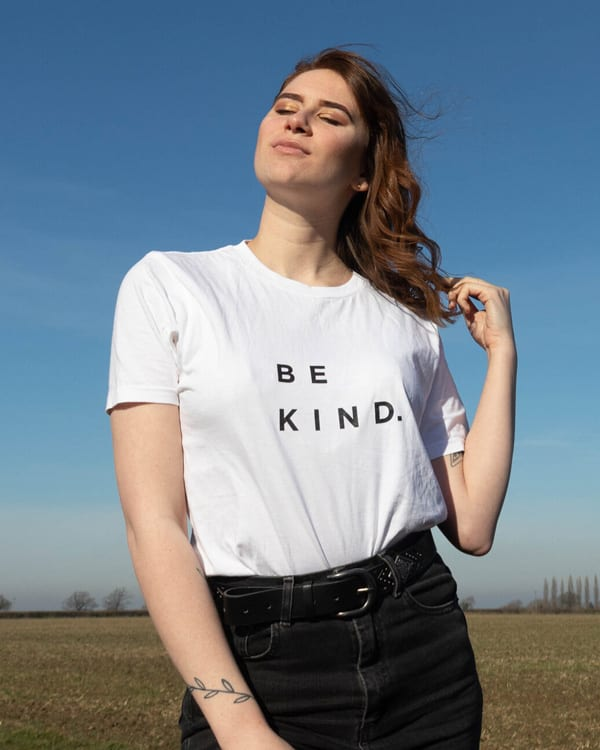 bronte wearing a white t shirt which says be kind on