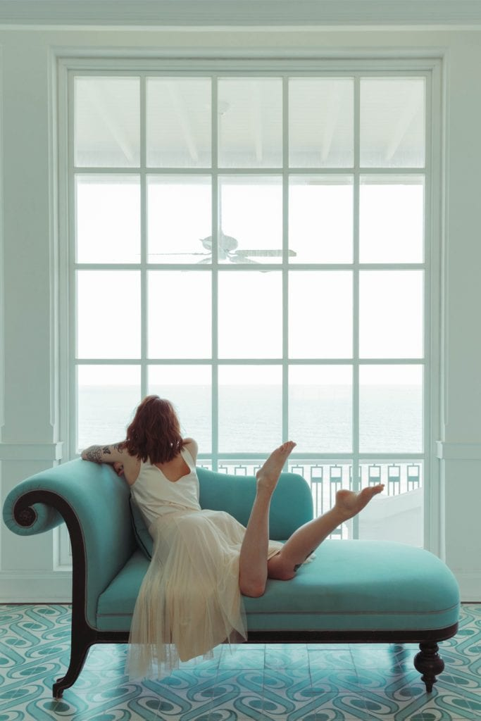 Girl on settee infront of double height windows
