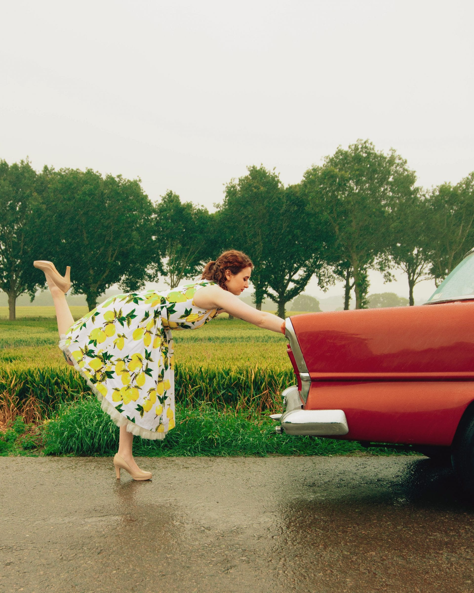 A girl pushing a broken down vintage car in a blog about feminism